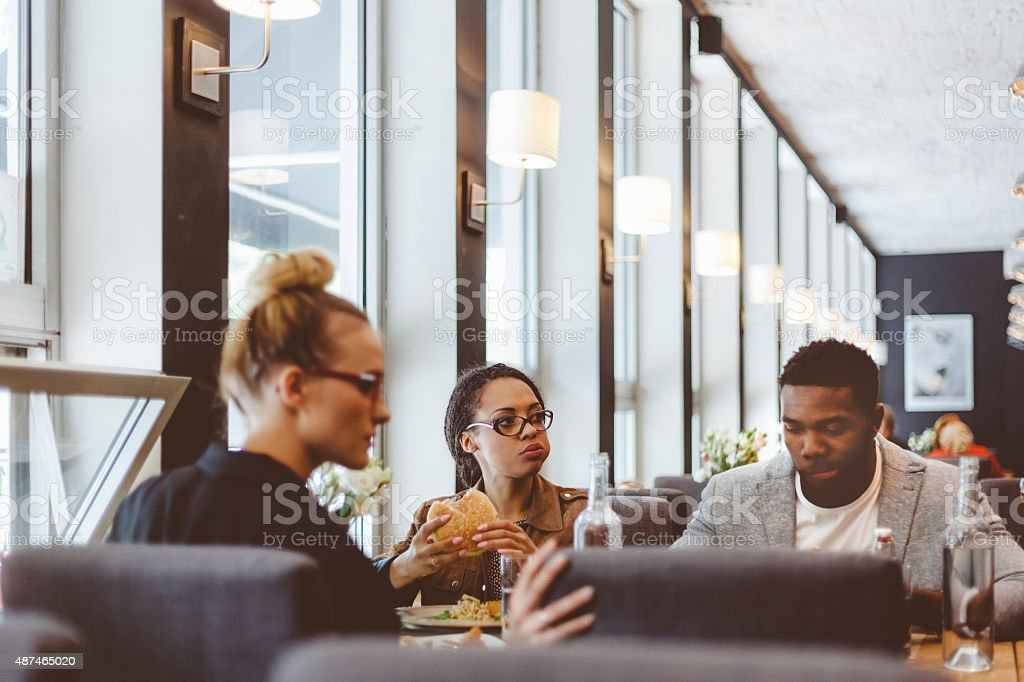 Multi ethnic group of friends having lunch in a restaurant stock photo