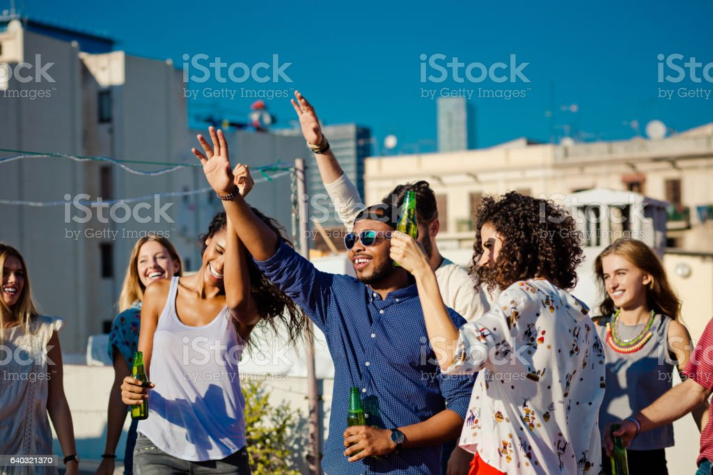 Multi ethnic group of happy friends at rooftop party stock photo