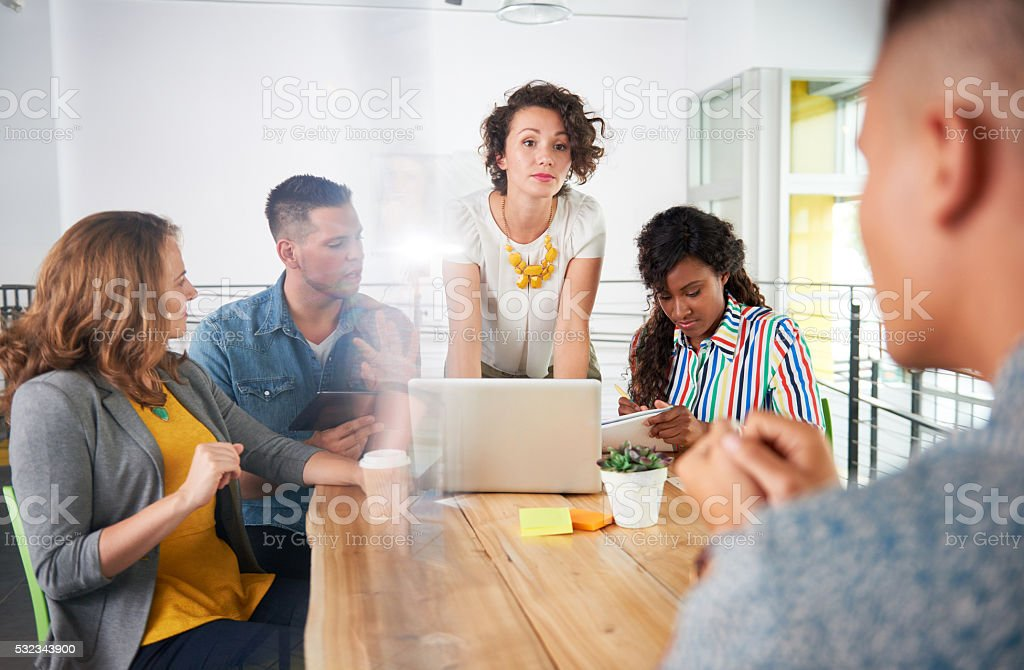 Multi ethnic group of succesful creative business people using a stock photo