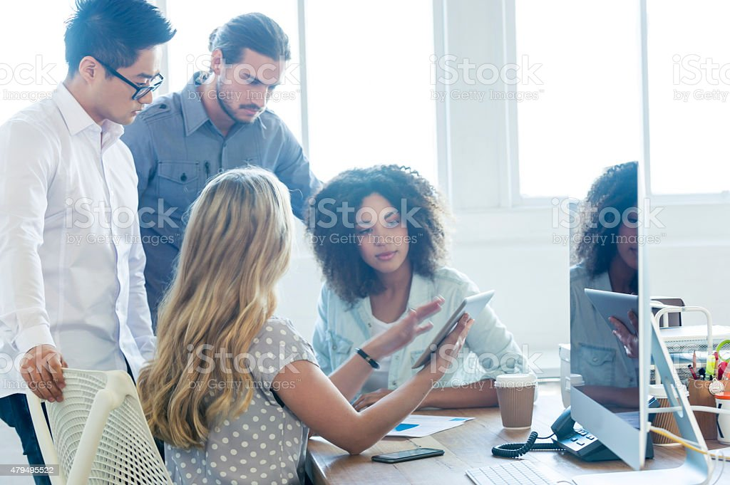 Multi ethnic group of young business people using technology stock photo