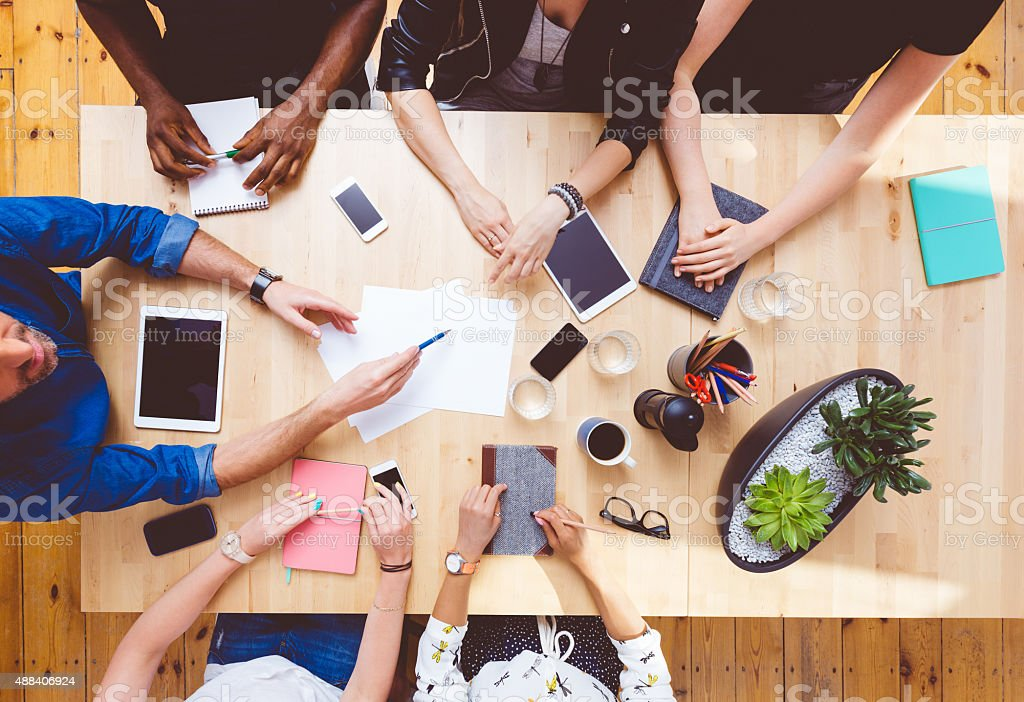 Multi ethnic team brainstorming, high angle view on the table stock photo