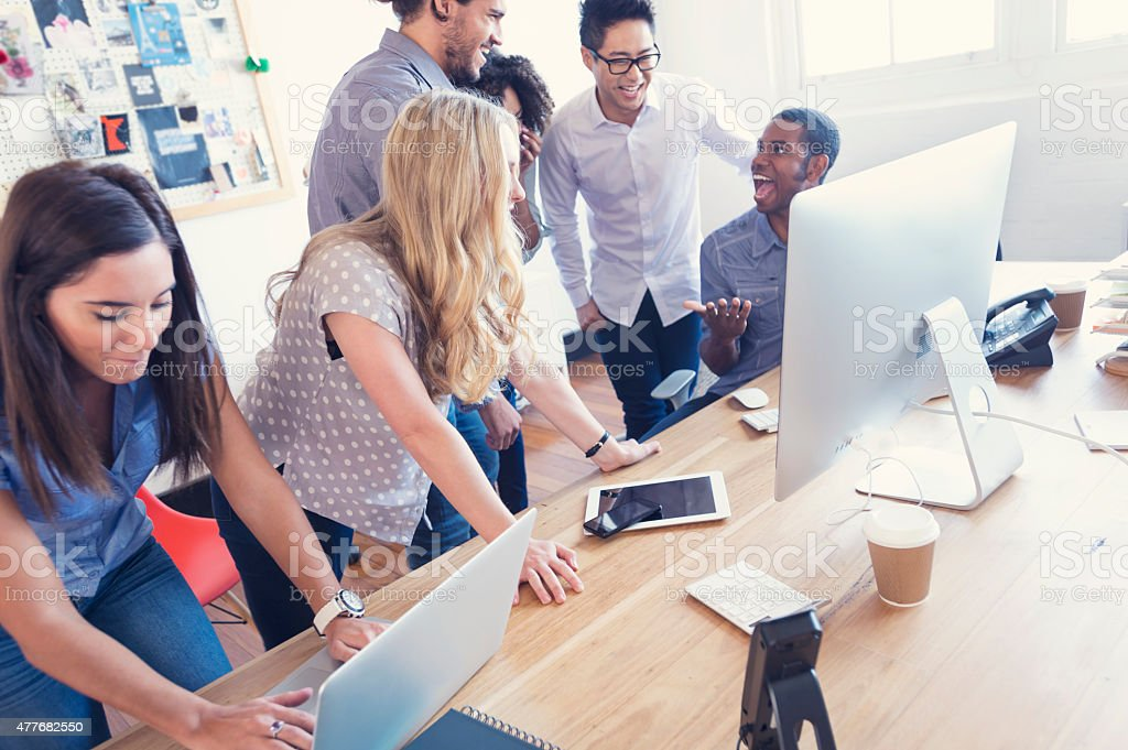 Multi ethnic young business team working on computers. stock photo