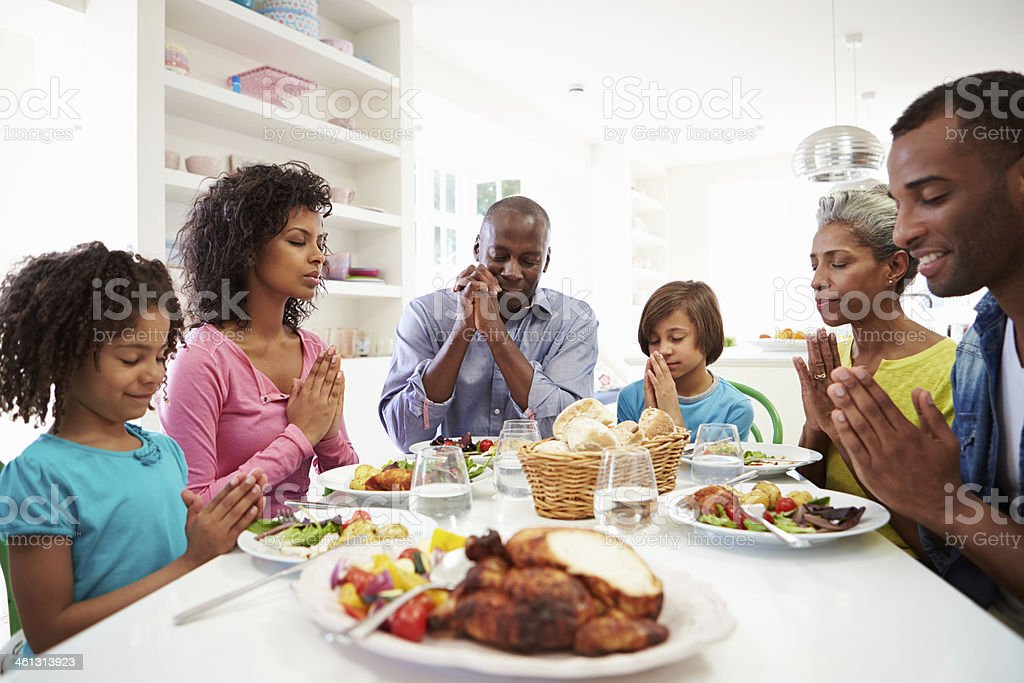 Multi Generation African American Family Praying At Home stock photo