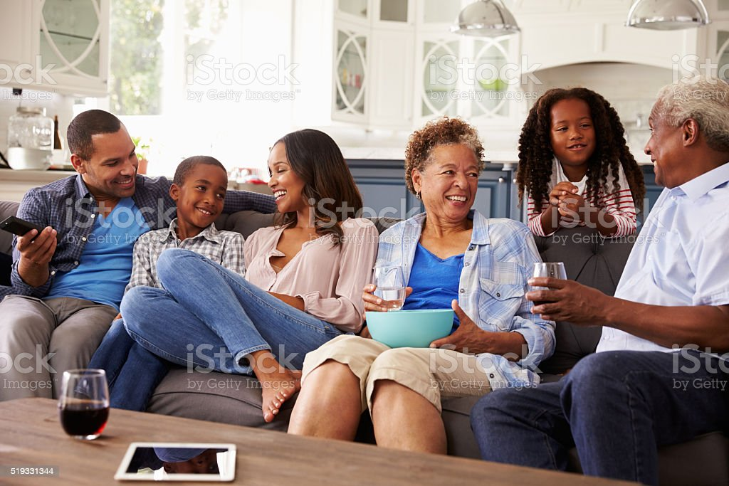 Multi generation black family talking together while watching TV stock photo