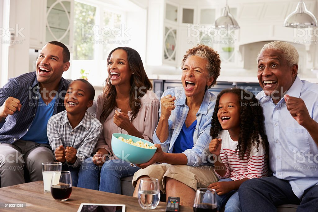 Multi generation black family watching sport on TV at home stock photo
