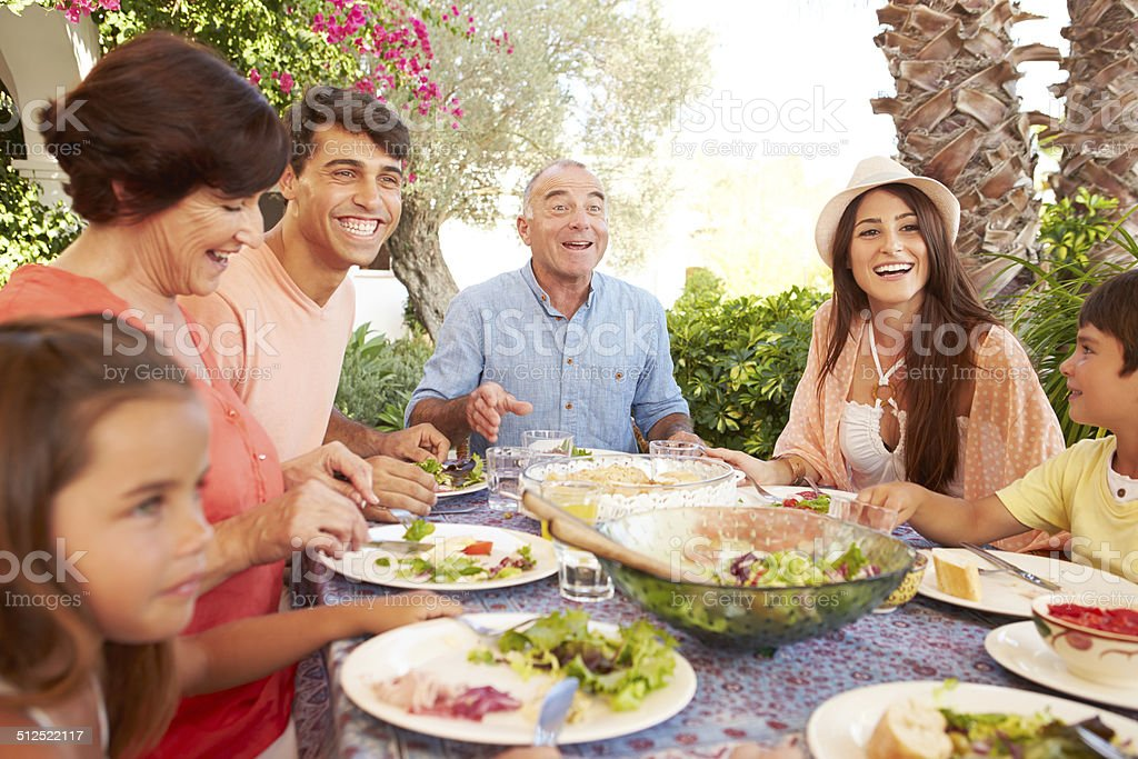 Multi Generation Family Enjoying Meal On Terrace Together stock photo