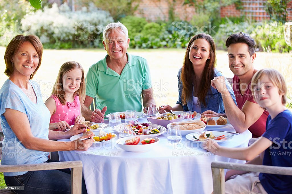 Multi Generation Family Enjoying Outdoor Meal Together royalty-free stock photo