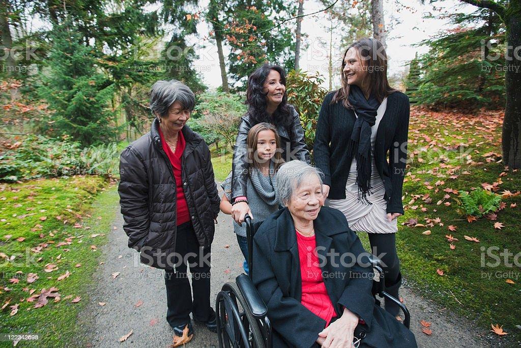 Multi generation family pushing senior woman in wheelchair stock photo