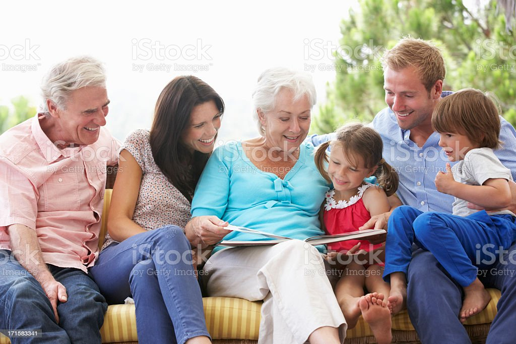 Multi Generation Family Reading Book On Garden Seat stock photo
