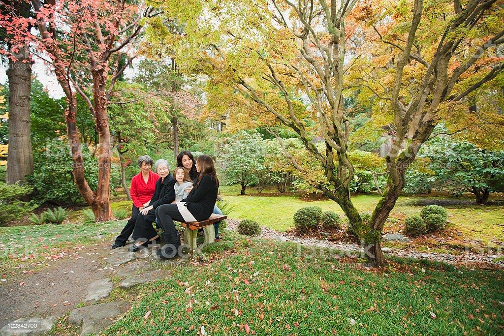 Multi generation family sitting in park stock photo