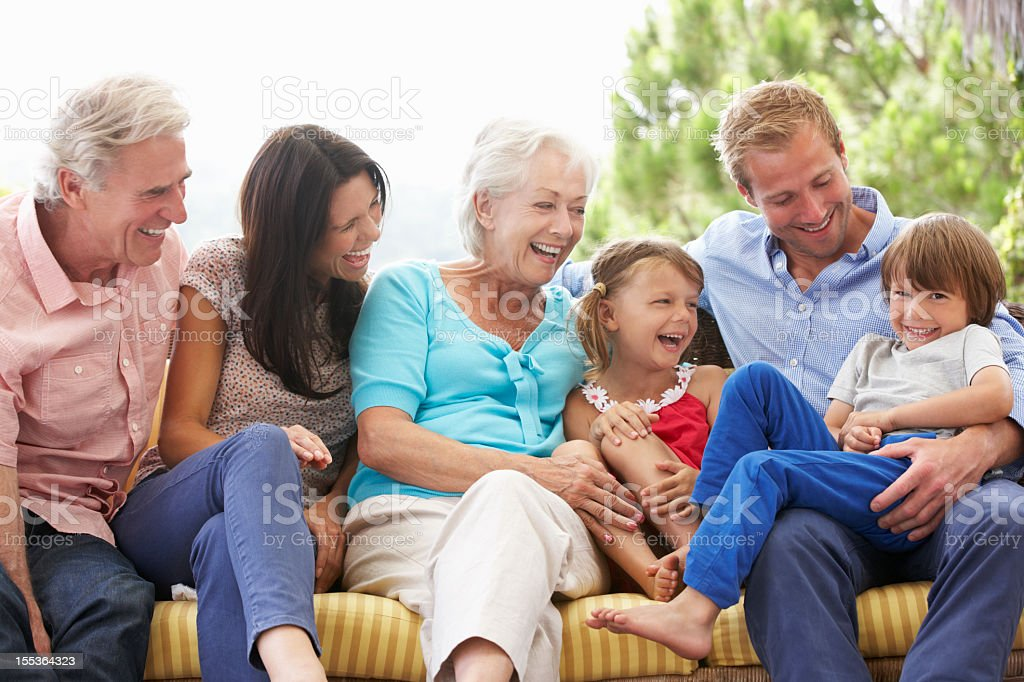 Multi Generation Family Sitting On Garden Seat stock photo