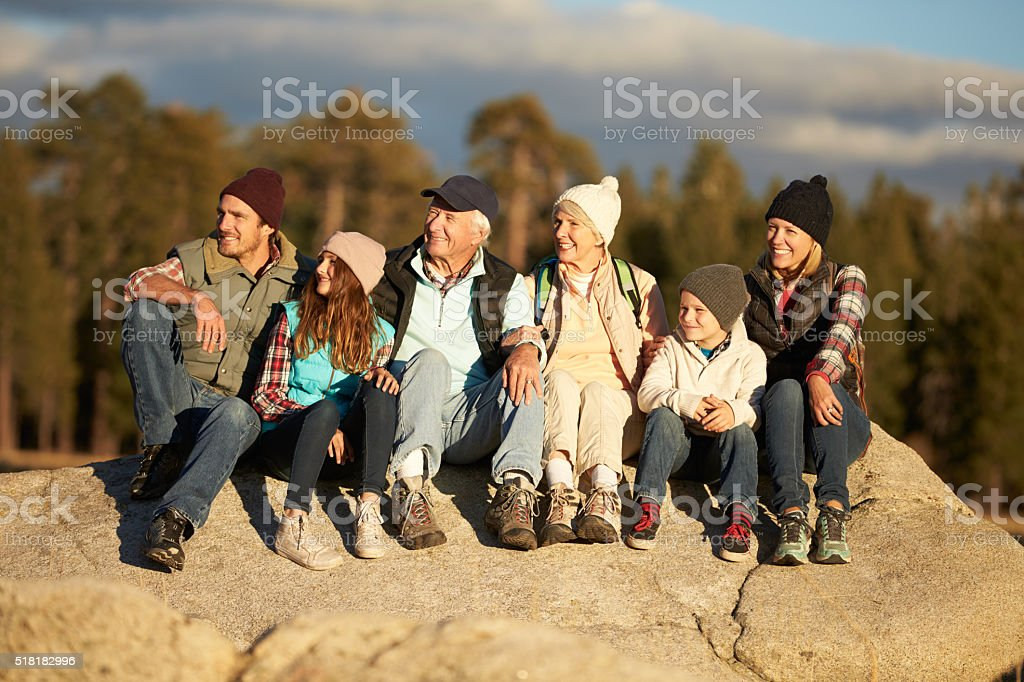 Multi generation family sitting on rocky outcrop near a forest stock photo
