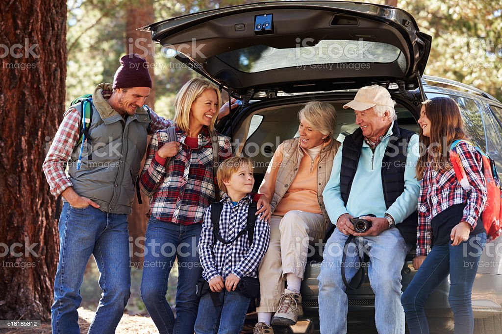 Multi generation family standing by a car before forest hike stock photo