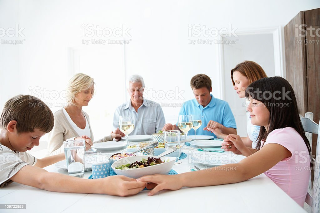 Multi generatonal family praying before lunch stock photo