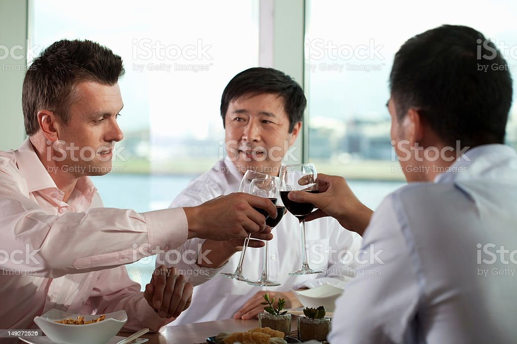 Multi racial businessmen toasting with wine stock photo