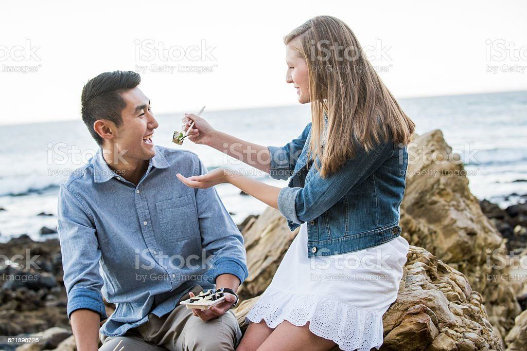 Multi Racial Couple Eating Sushi at the Beach stock photo