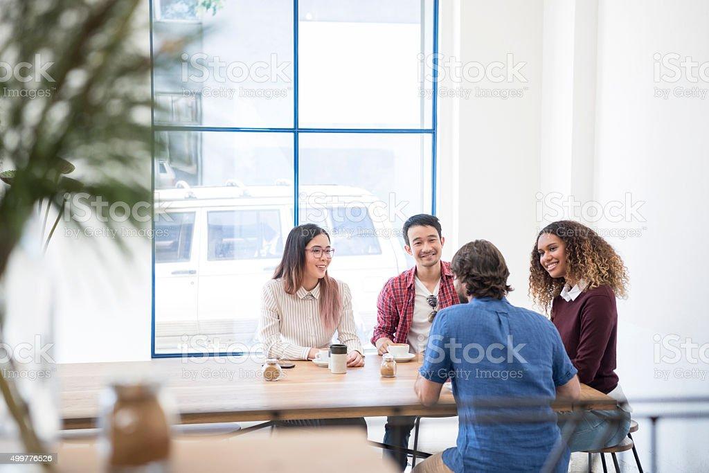 Multi racial group in modern cafe taking coffee break stock photo