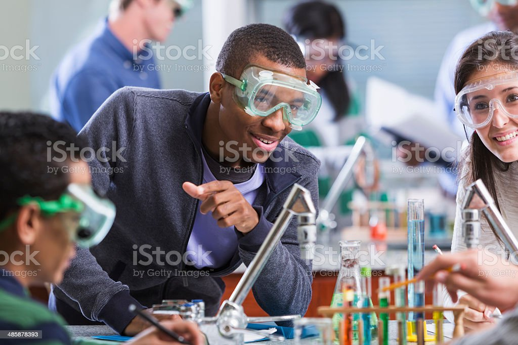 Multi racial students in chemistry class wearing safety glasses stock photo