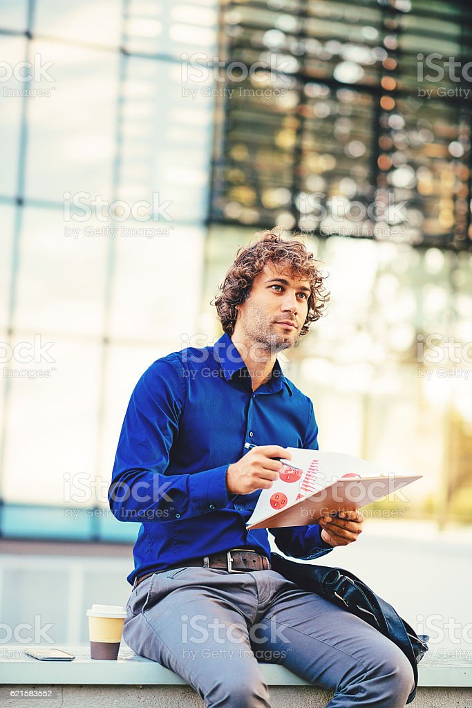 Multi tasking businessman dealing with financial instruments stock photo