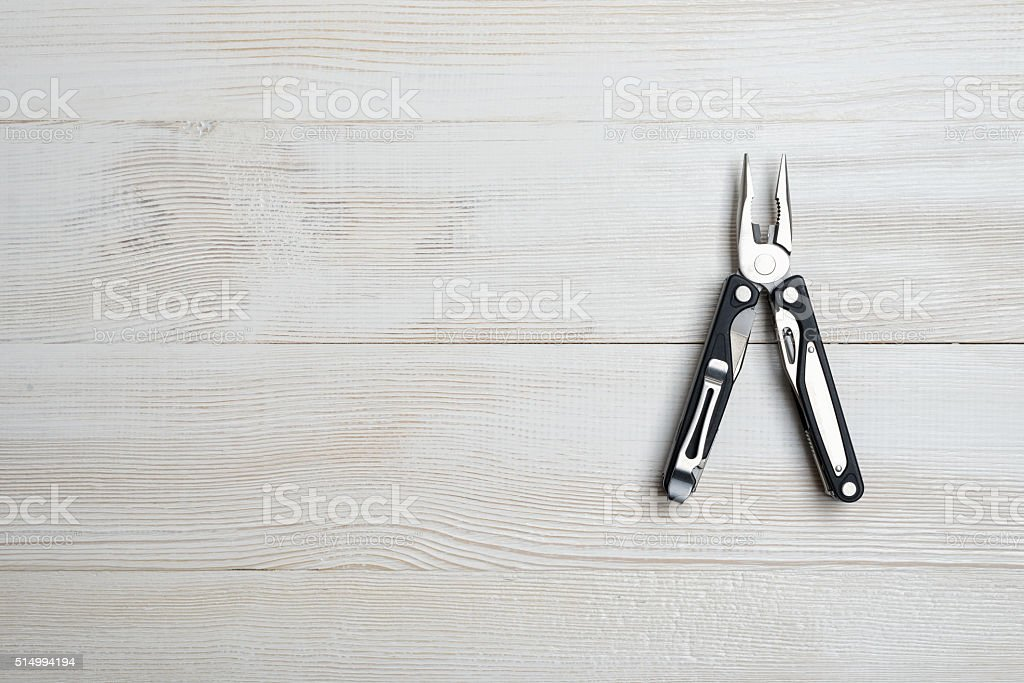 Multi tool with black handles on a white wooden background stock photo
