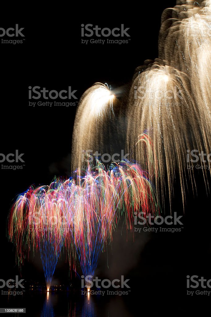 Multicolor and white fireworks on a lake royalty-free stock photo