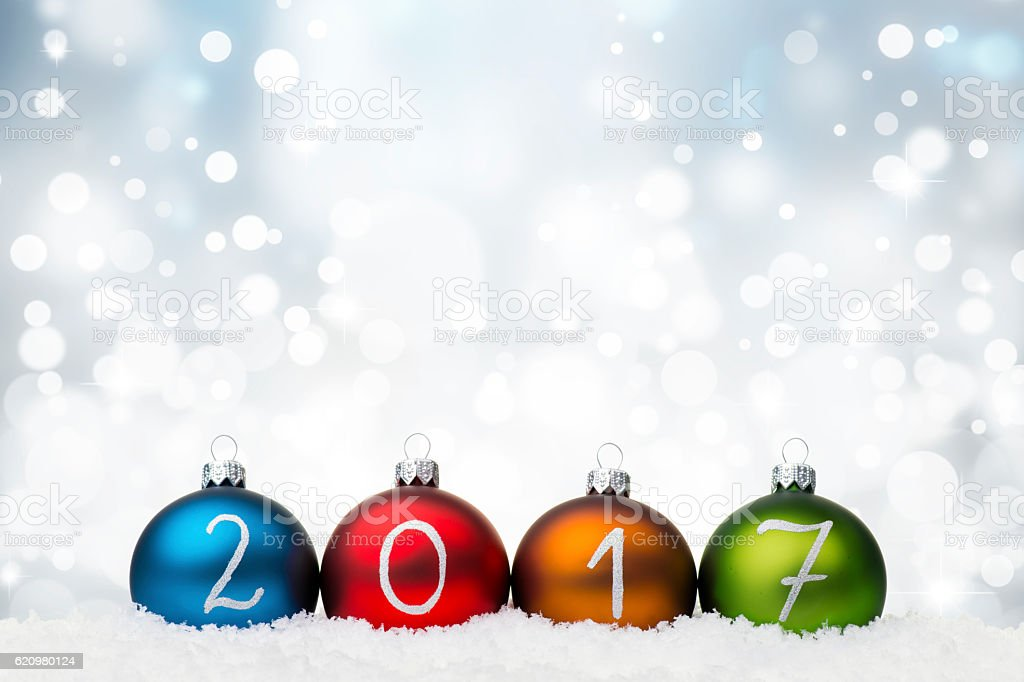 Multicolor Baubles arranged in 2017 year on snow stock photo
