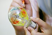 Multicolor painting light bulb in hand
