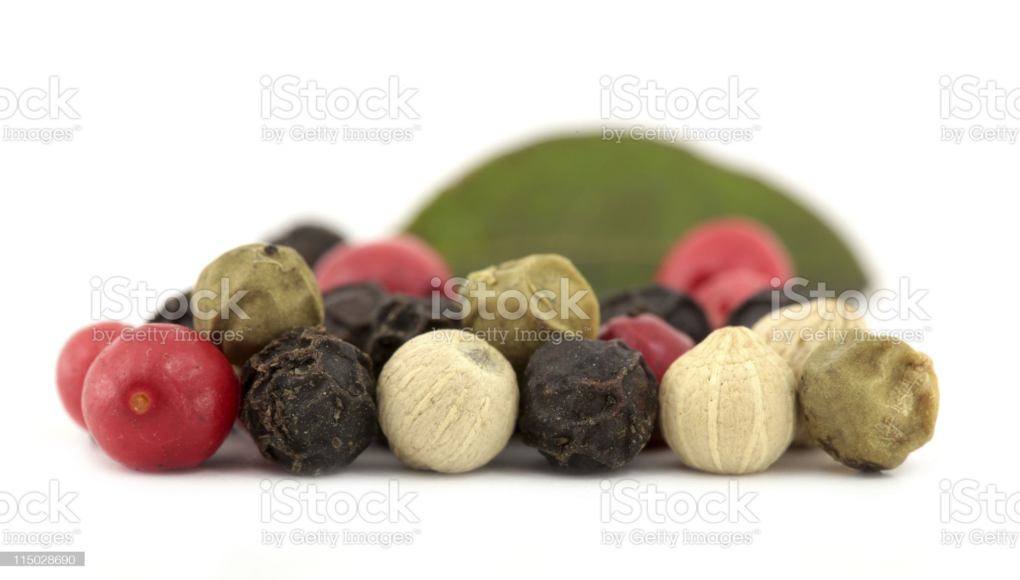 Multicolor peppercorns macro with green leaf royalty-free stock photo
