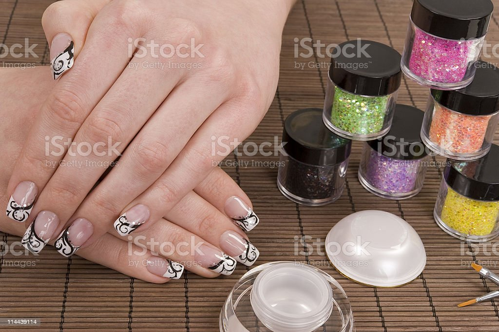 Multicolor shiny nail polish on bamboo mat with white hands stock photo