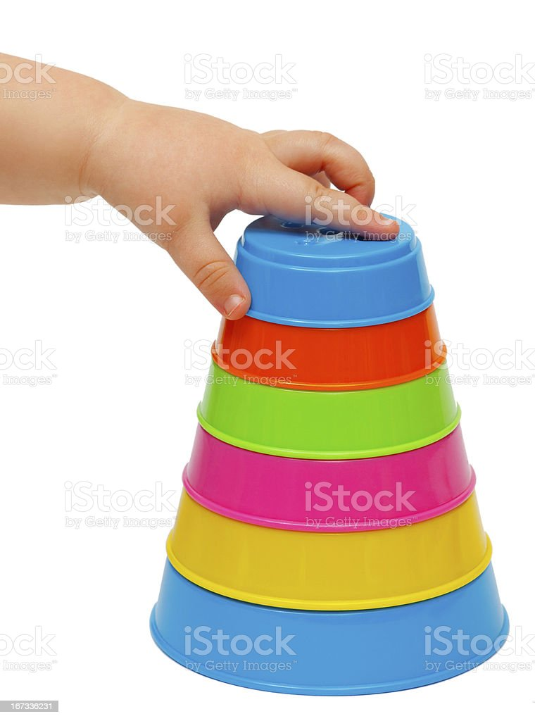 Multicolor tower of cups and child's hand royalty-free stock photo