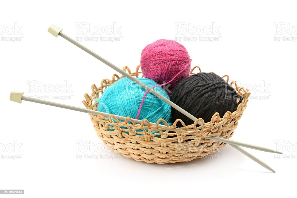 Multicolored balls and needles in basket stock photo