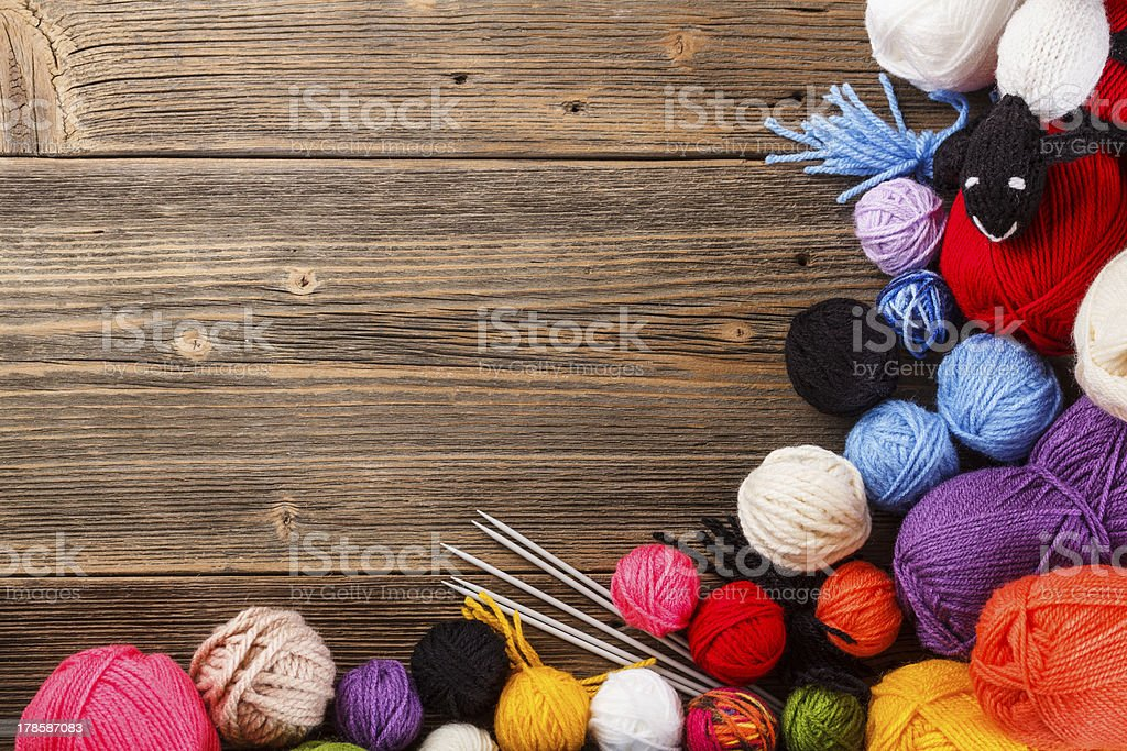 Multicolored balls of yarn bordering a wood background stock photo