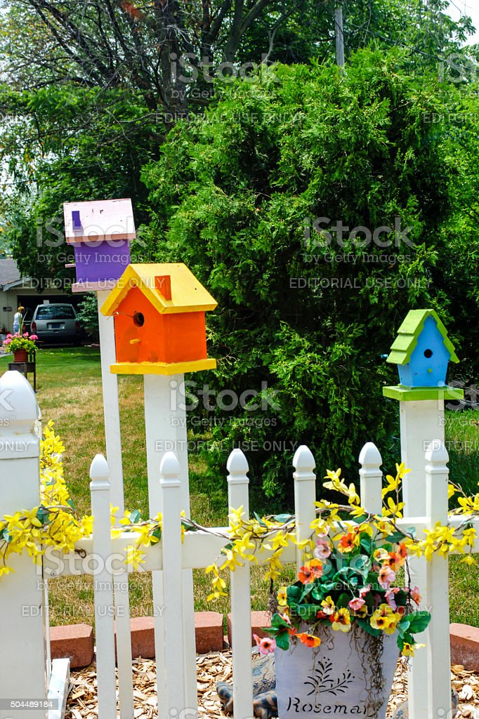 Multi-colored birdhouses in a front yard in Michigan stock photo
