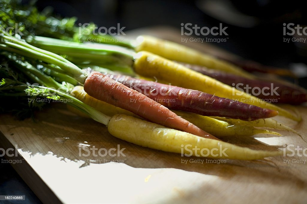 Multicolored carrots on a wooden cutting board stock photo