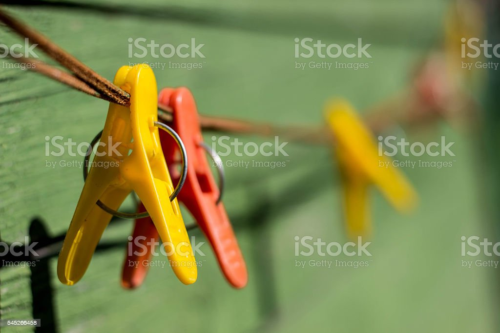 Multi-colored clothespins on rope stock photo