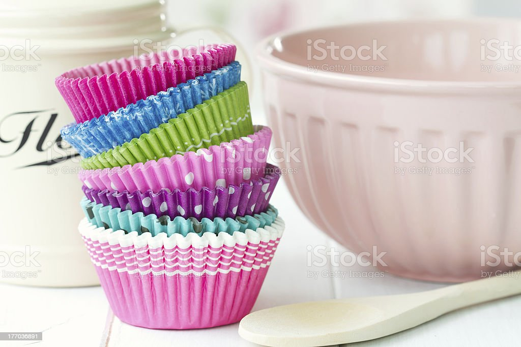 Multicolored cupcake cases in a stack next to baking tools stock photo