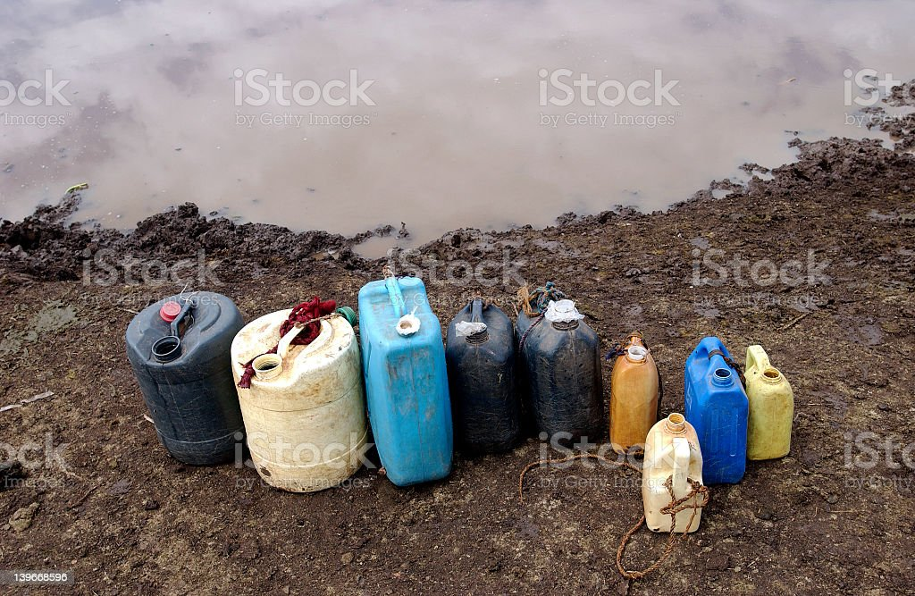 Multicolored dirty plastic jugs in a row on the dirt stock photo