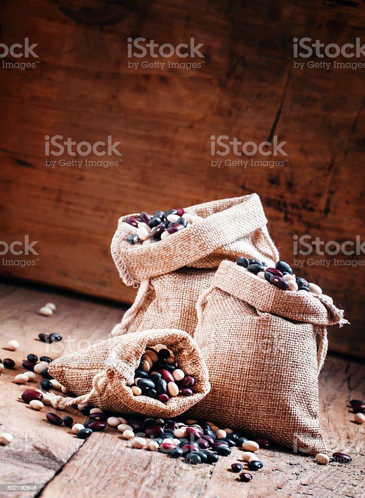multi-colored dry beans in burlap sacks stock photo