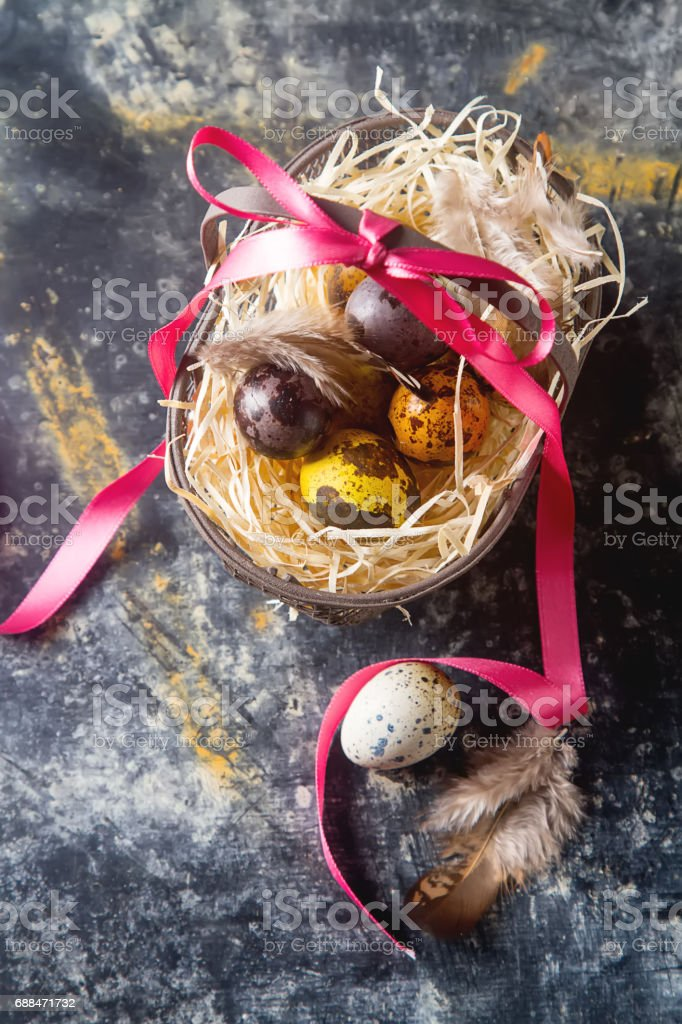 Multi-colored Easter egg. Quail eggs with feathers in basket. Dark background. Spring holiday. stock photo