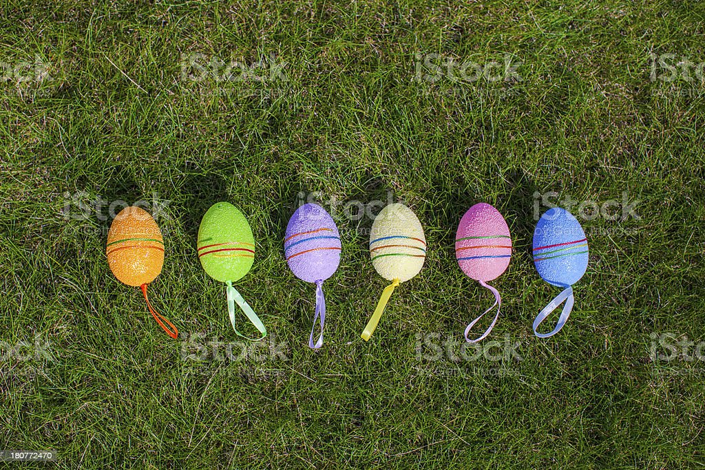 Multi-colored Easter eggs on green grass royalty-free stock photo