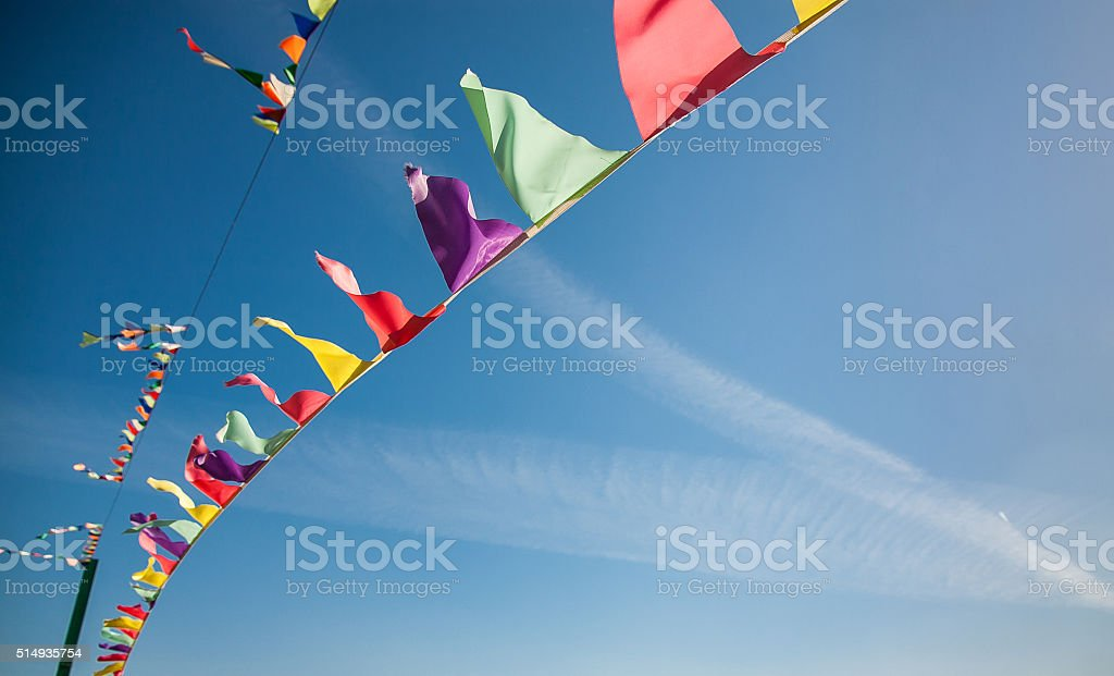 Multicolored flags against the blue sky with traces from planes stock photo