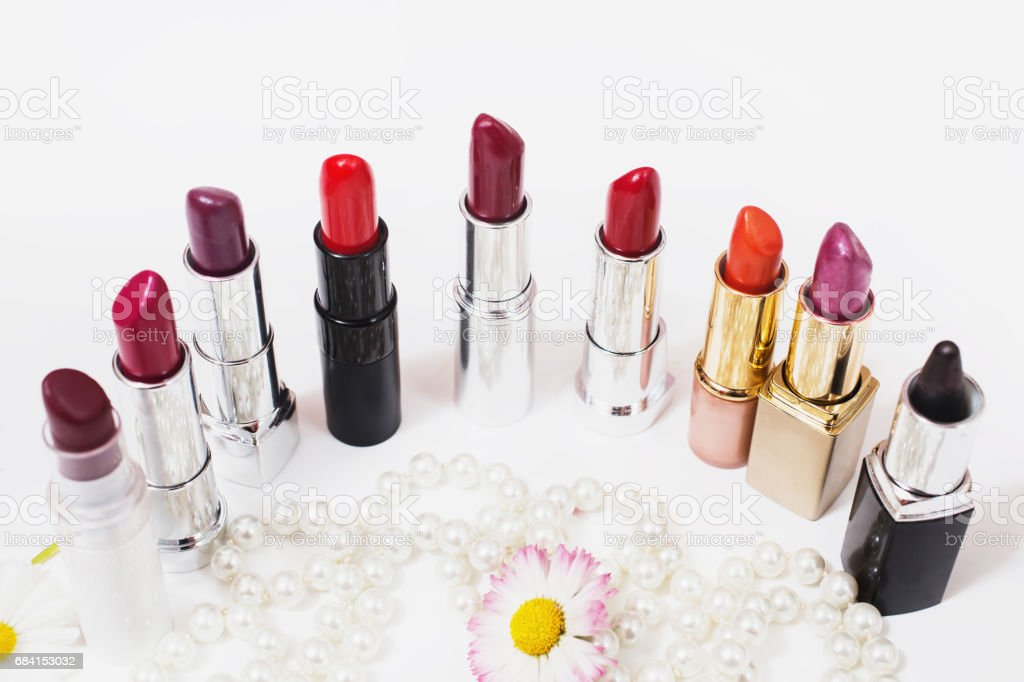 Multicolored glossy lipstick on white background. Wild purple flower on a white surface. Female white beads. Cosmetic products for painting lips. View from above. Makeup accessories stock photo