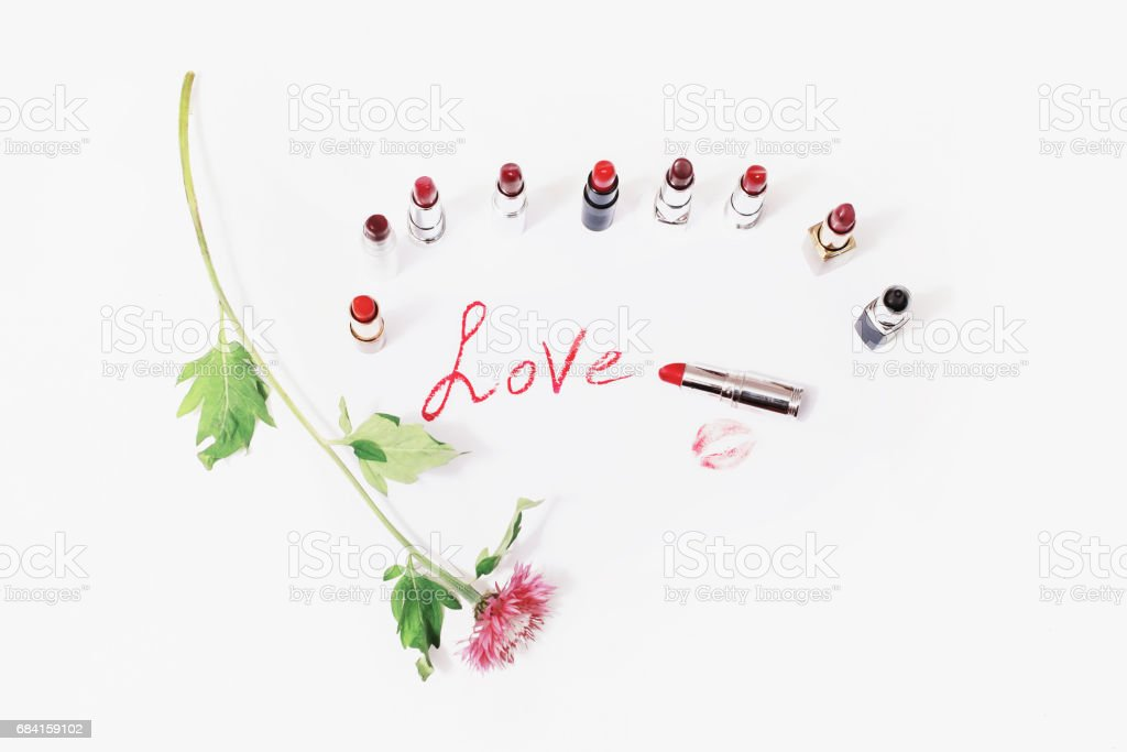 Multicolored glossy lipstick on white background. Wild purple flower on a white surface. Lips kiss on paper. Cosmetic products for painting lips. The word love written in lipstick on a light surface stock photo