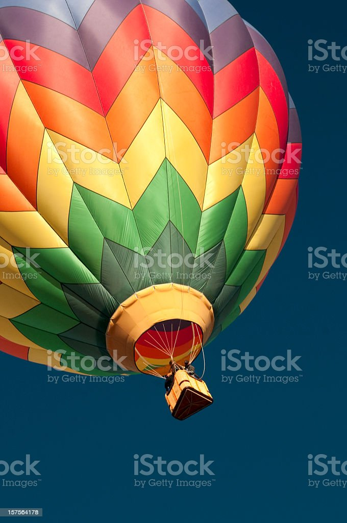 Multicolored hot air balloon isolated against the blue sky royalty-free stock photo