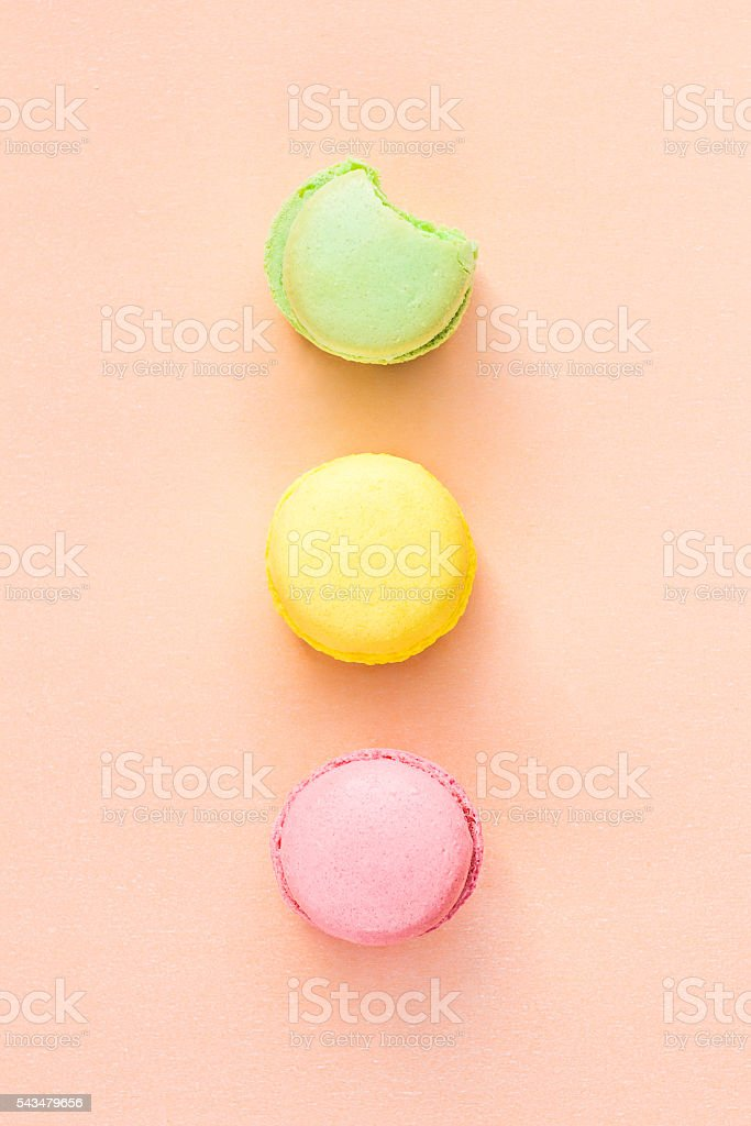 multicolored macaroon on beige paper background, flat lay, top view stock photo