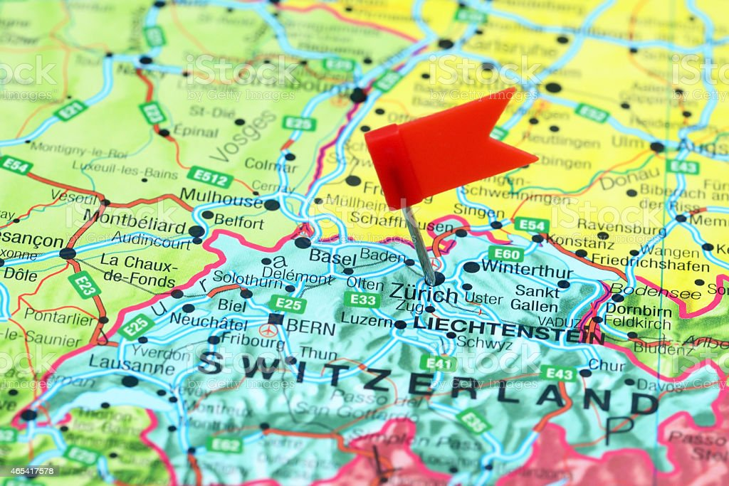 Multicolored map of Europe with a red flag pin in Zurich stock photo