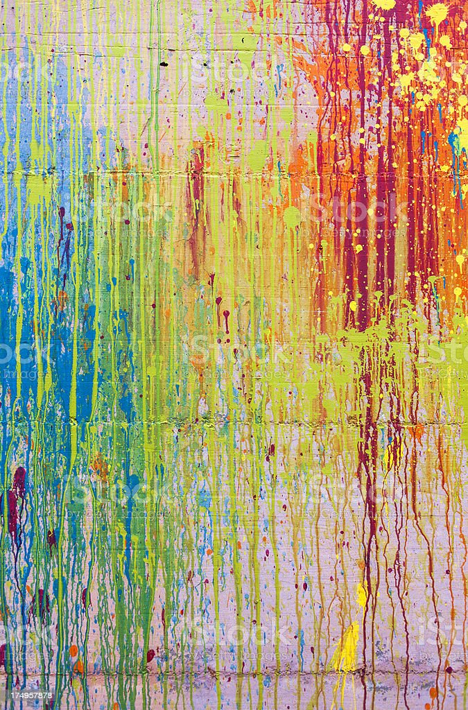 Multi-colored paint splatters running down a wall stock photo