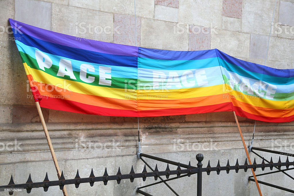 multicolored peace flag during a demonstration of pacifists in a stock photo