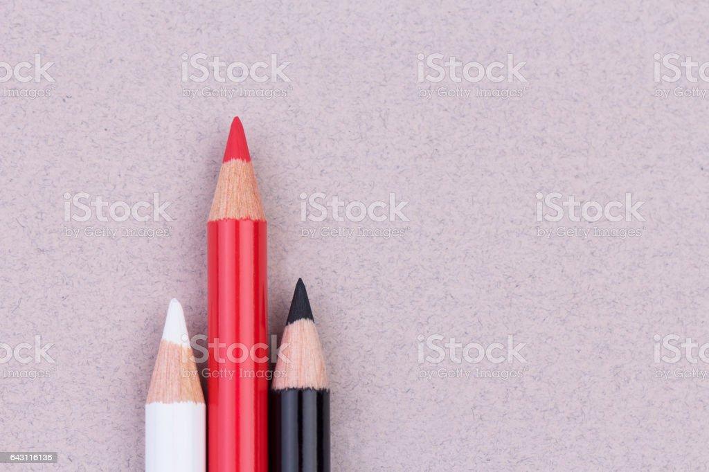 Multicolored pencils on beige pastel paper coarse grain grunge texture stock photo