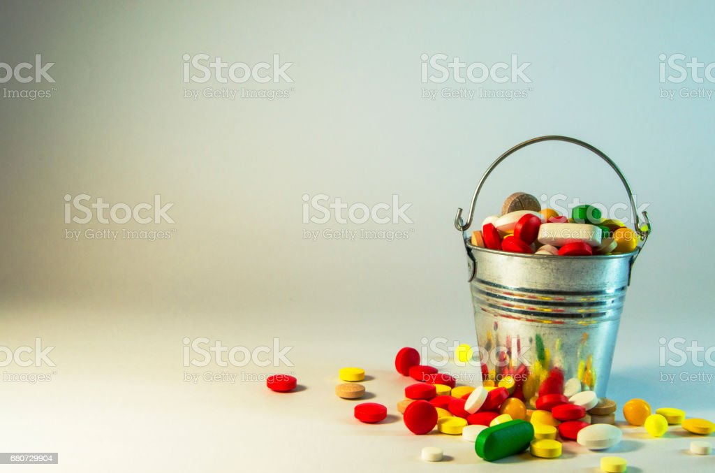 multicolored pills are in a metal bucket standing on a white background stock photo